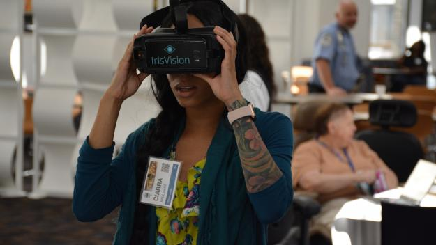 photo of a woman experiencing VR with other exhibit booths around behind her.