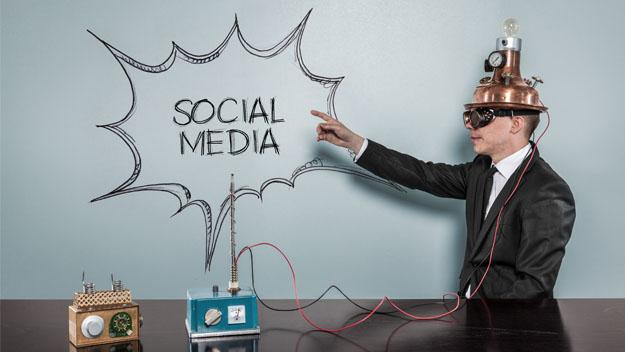 Man points at social media words on white board with old fashioned technology on his head.