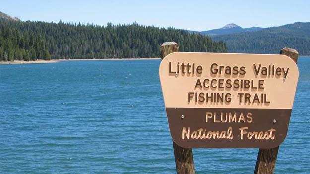 Photo of national forest sign with lake and mountains in background