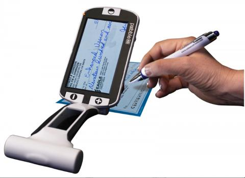Photo of portable video magnifier standing vertically and use to sign a check book.