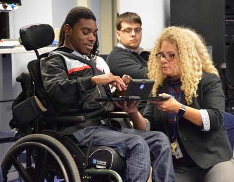 Michelle Sherbondy, a deaf USDA employee, is kneeling and demonstrating a face-to-face communicator to a young man in a wheelchair.  Another young man sits behind them watching the demo of how a deaf person and hearing person can communicate using the tool.