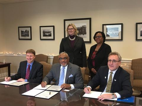 USDA's Malcom Shorter (sitting in the middle) with Alison Levy and Marsha Wiggins (standing behind) at the disability inclusion MOU signing ceremony with Derek Shields from NDMC (L) and Andy Imparato (AUCD) on the right.